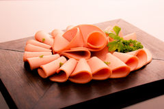 Mortadella. Wooden chopping board with sliced mortadella royalty free stock photo