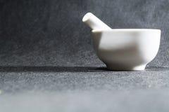 Mortaio bianco con un pestello da porcellana Una ciotola bevente per schiacciare delle spezie Priorità bassa nera Utensili della  fotografia stock