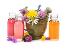Mortaio con i fiori freschi e l'olio essenziale Fotografia Stock