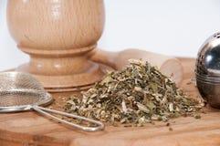 Mortaio di legno con tè fatto dal filtro del metallo e del basilico Immagini Stock Libere da Diritti