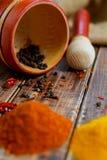 Mortaio e pestello con pepe, peperoncino rosso vicino alle spezie sulla tavola di legno Fotografia Stock