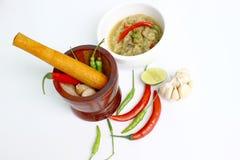 Mortaio ed ingredienti per la cottura e salsa di peperoncino rosso su fondo bianco Immagine Stock
