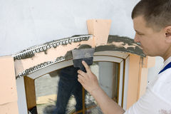 Mortar. Plasterer inflicts mortar on architectural element Stock Photo