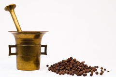 Mortar and allspice. Brass mortar and allspice isolated on white background stock photos
