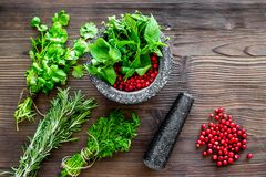 Mortar with berries, herbs and spices ingredients on wooden background top view Royalty Free Stock Photos