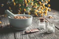 Mortar of dried healing herbs, homeopathic globules and bunch of chamomile plant. Homeopathy and herbal medicine royalty free stock photography