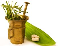Mortar with herbal, and pills. Stock Photo