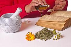 Mortar with herbs. Book and a women with a spoon and medicine drops Stock Image