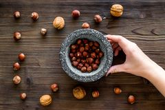 Mortar with nuts, herbs and spices ingredients on wooden background top view Royalty Free Stock Image
