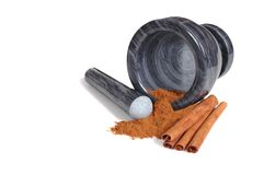 Mortar with pestle and cinnamon. Mortar and pestle with cinnamon sticks and powder Royalty Free Stock Photo