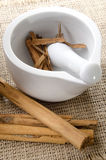 Mortar and pestle with cinnamon on jute Stock Photo