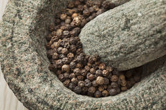 Mortar and pestle with dried black pepper Stock Photo