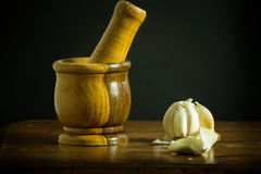 Mortar and Pestle with garlic on a wooden table Stock Photo