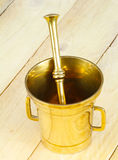 Mortar and pestle. Golden Mortar and pestle on wood Stock Photos