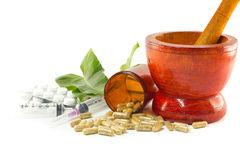 Mortar and pestle with herb capsules spilling out of bottle Stock Photos
