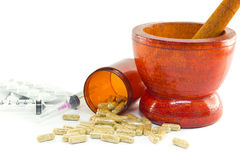 Mortar and pestle with herb capsules spilling out of bottle Royalty Free Stock Photos