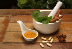 Mortar and pestle with herb and pills Stock Photo