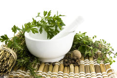 Mortar and pestle with herbs. Spices, bamboo mat Stock Photography