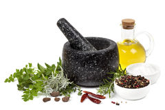 Mortar and Pestle with Herbs and Spices. Black marble mortar and pestle, with herbs, spices and olive oil,  on white Royalty Free Stock Photos