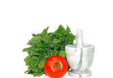 Mortar and Pestle isolated. Rapini and tomato beside marble mortar and pestle, isolated on white Royalty Free Stock Photography