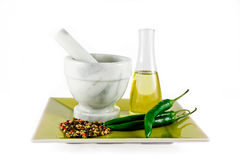 Mortar and pestle with oil and spices isolated. Mortar and pestle on a plate with bottle of oil, chillies and spices isolated on white background Stock Photography