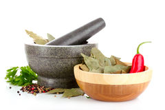 Mortar and pestle, parsley, pepper on white Royalty Free Stock Images