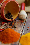 Mortar and pestle with pepper, chili near spices on the wooden table. Stock Photography