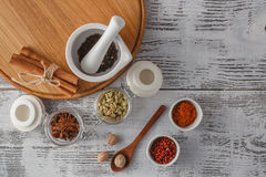 Mortar and pestle with pepper and spices on wooden table Stock Image