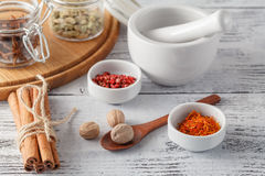 Mortar and pestle with pepper and spices on wooden table Stock Photos