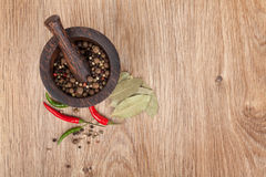 Mortar and pestle with red hot chili pepper and peppercorn Stock Images
