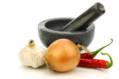 Mortar and pestle and some fresh vegetables. On a white background stock photo