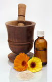 Mortar and Pestle spa display. Old wooden Mortar and Pestle with bottle containing aromatherapy oil and flowers with bath salts for decoration Stock Photo