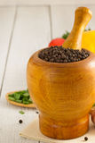 Mortar with pestle and spices on wood Royalty Free Stock Photography