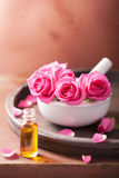 Mortar with rose flowers and essential oil Royalty Free Stock Image