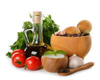 Mortar with spices, olive oil and fresh vegetables Stock Photography
