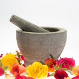 Mortar of stone in rose petals. And in front of a white background Stock Photos