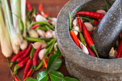 Mortar with thai spices and herb. (garlic, chili pepper, lemon grass, kaffir lime leaf Stock Photos