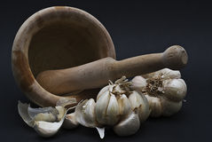 Mortar to mash garlic. Mortar and garlic on a black background Royalty Free Stock Images