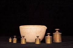 Mortar and weights. Old time pharmacy mortar with brass weights Royalty Free Stock Photo