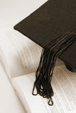 Mortarboard and Book. In Sepia Tone Stock Image