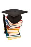 Mortarboard on books stack. A mortarboard on a book stack, symbol photo for education and skills Stock Photo