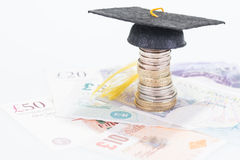 Mortarboard on british coins and pounds sterling banknotes Stock Photo