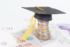 Education costs. Mortarboard on british coins and pounds sterling banknotes close-up stock images