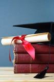 Mortarboard, desfile y libros de la graduación fotografía de archivo libre de regalías