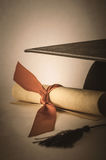 Mortarboard and Diploma Scroll Tied with Ribbon with Vintage Eff Stock Images