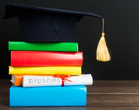 A mortarboard and graduation scroll. Tied with red ribbon, on a stack of books royalty free stock images