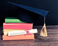 A mortarboard and graduation scroll Stock Image