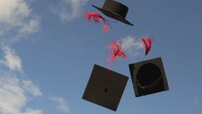 Mortarboards flying in blue sky, university tradition to throw academic caps up