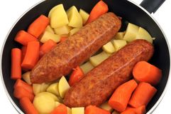 Morteau sausages with raw vegetables in a pan. Preparing a meal made from pork, potatoes and carrotsin closeup stock photography