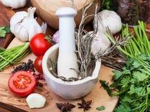 Mortel med mortelstöten och ört och kryddor på tabellen Arkivfoton